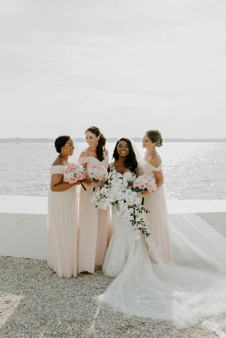 Bride and bridesmaids posing on waterfront