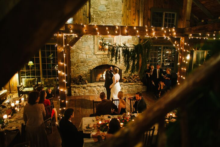 "Paula and Nik took their first dance to ""Wicked Games"" by James Vincent McMorrow in front of the stone fireplace. Surrounded by twinkling string lights, wooden accents and green foliage, the setting couldn't have been anymore romantic."
