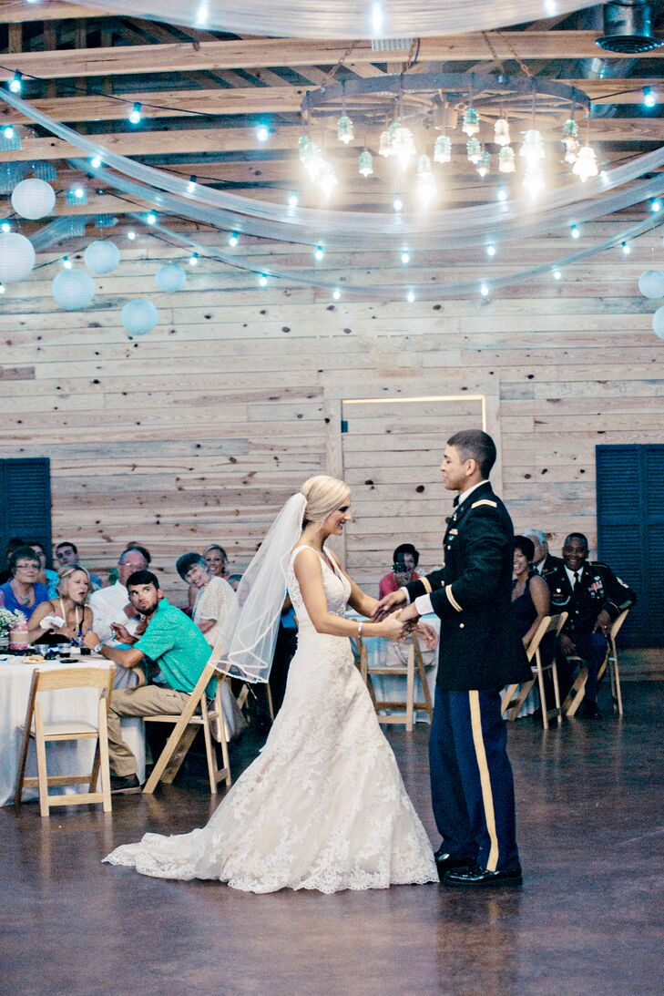 "For their first dance, Samantha and Chris selected ""I Don't Dance"" by Lee Brice. String lights and an iron chandelier created a romantic glow inside the rustic wooden reception barn."