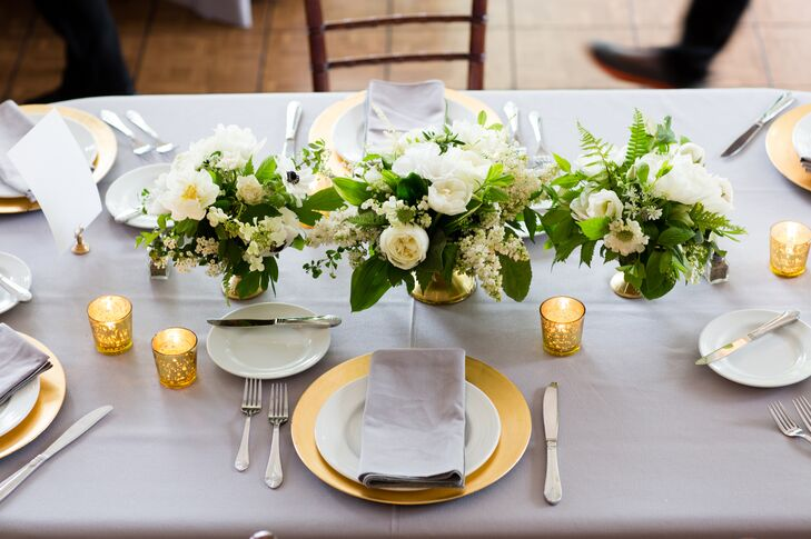 The flowers were the highlight of the reception decor with Sebesta Design creating opulent, romantic arrangements of oversized white blooms and cascades of lush greenery displayed in gilded compote vases. Flowers included ranunculus, astrantia, spirea, sweet peas, wildflowers, lisianthus, scabiosa, hellebores, stock, tulips, astilbes, mock orange blossoms, lysimachia and double peonies, while green blueberries, Solomon's seal, dusty miller, gardenia, clematis, jasmine vines, bleeding hearts, silver dollar, lamb's ear, sea star ferns and viburnum served as filler. Each elegant design differed slightly from the next, giving the reception space an eye-catching, textured look.
