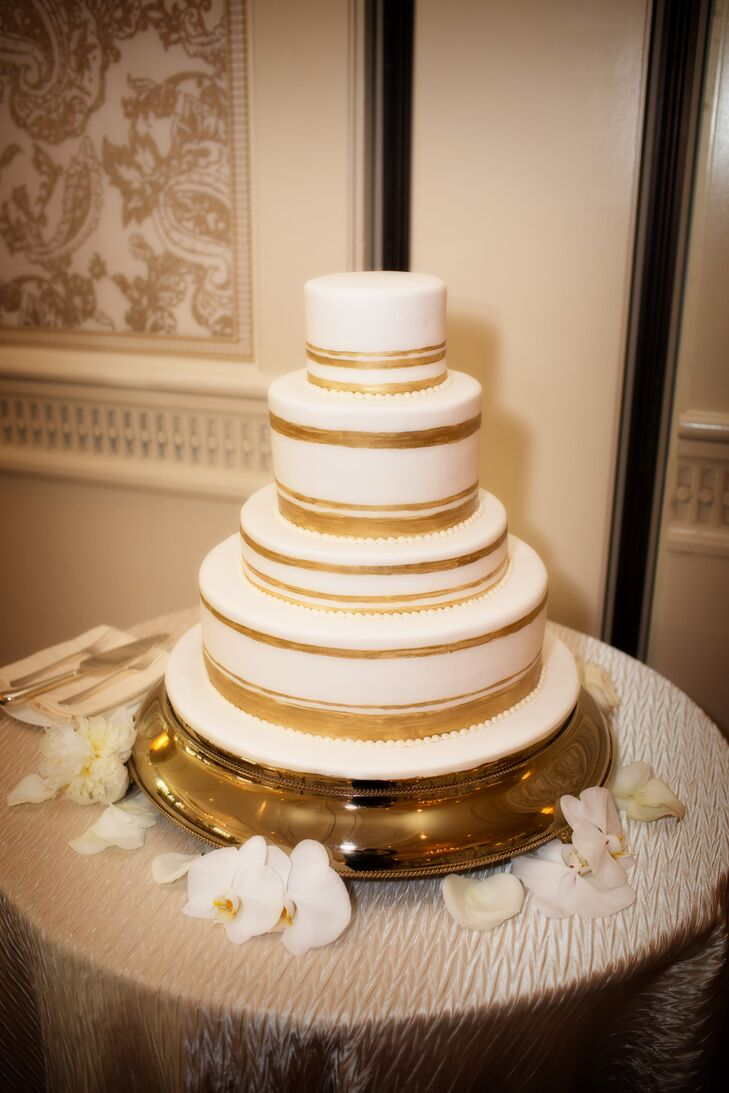 The round layers of the cannoli flavored wedding cake were finished with painted gold stripes.