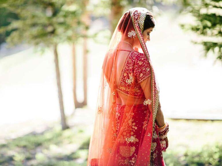 Bride wearing red lehenga with sheer veil
