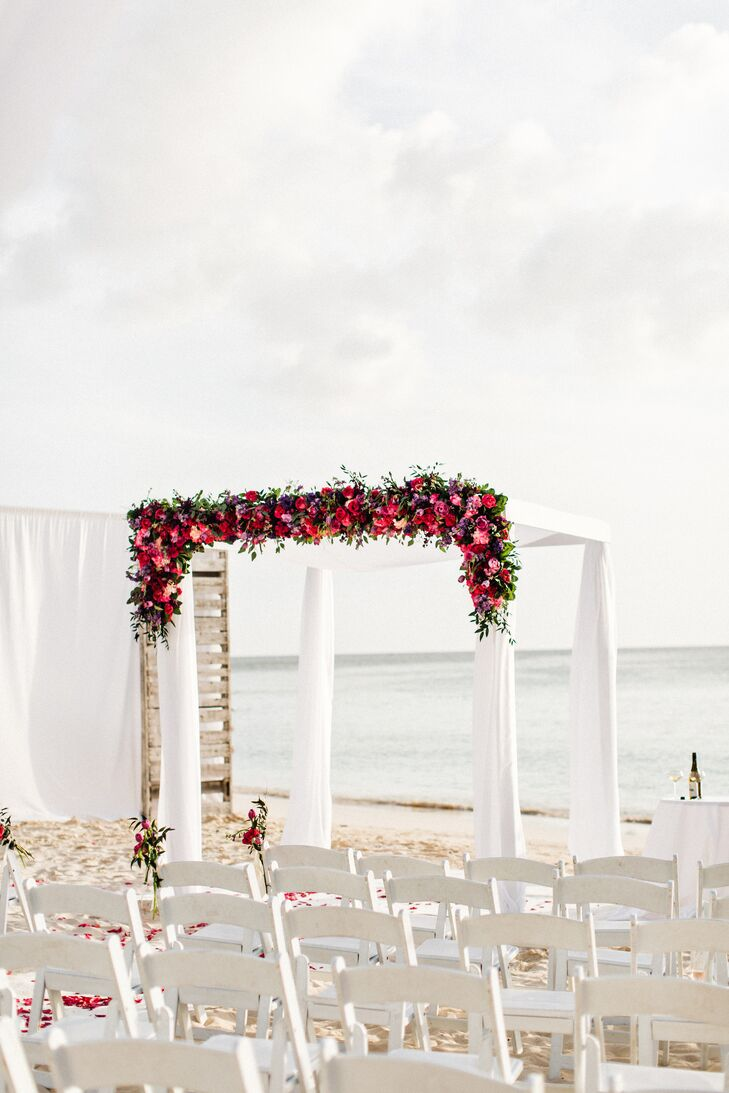Chuppah Draped in White Fabric and Pink, Purple and Peach Flowers
