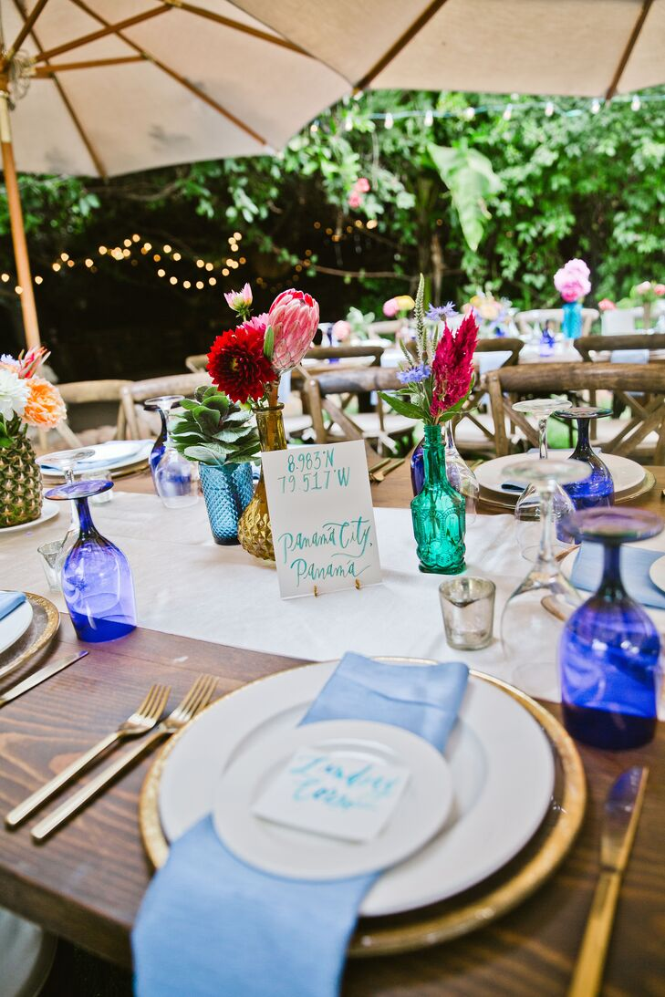 Rustic wooden farm tables were decorated with blue wine bottles, eucalyptus leaves, abalone shells, silk dupioni table runners, light blue napkins, cracked gold chargers, gold flatware and cobalt blue water glasses.