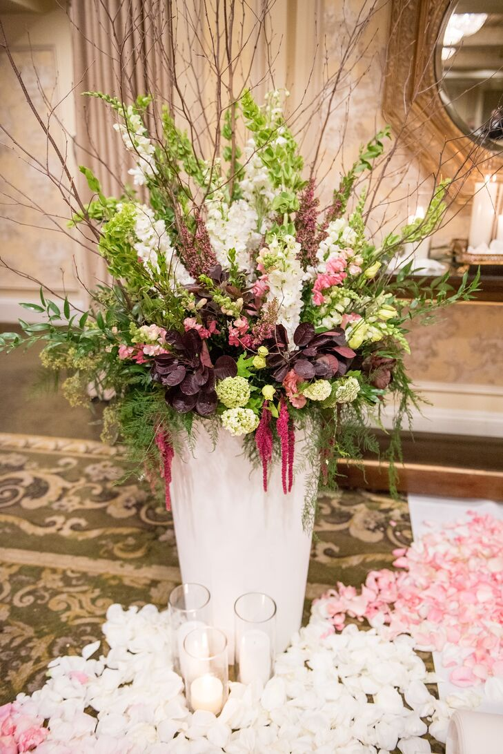 Ceremony decor featured large white vases bursting with green hydrangeas, deep purple petals, ivory blooms, greenery and whimsical branches. The aisle was lined with champagne and blush rose petals and accented with white candles.