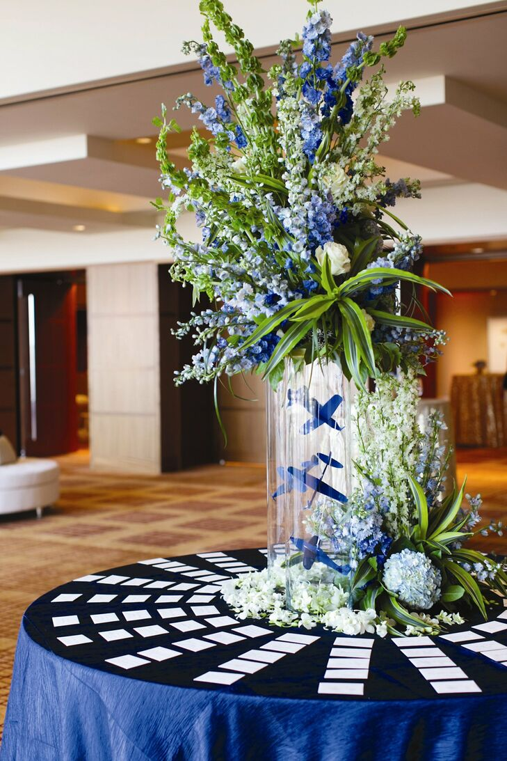 At the center of the escort card table was an elaborate floral display of white and blue hydrangeas, delphiniums, bells of ireland and orchids arranged over modern glass vases filled with blue airplanes, a nod to Phil's work in the aerospace industry.