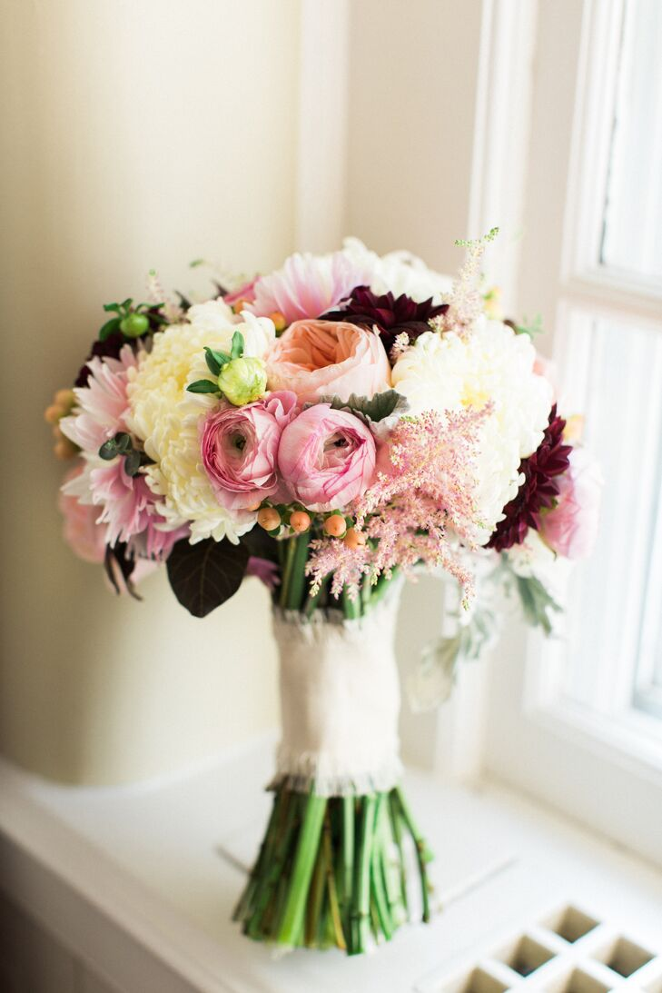 To complement her dramatic burgundy accessories, Megan's bridal bouquet featured a vibrant mix of pink garden roses, ivory mums and dramatic wine-colored dahlias. For a hint of rustic flair, the arrangement was gathered together with a piece of white linen cloth.