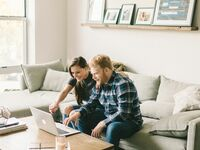 Engaged couple wedding planning on laptop at home