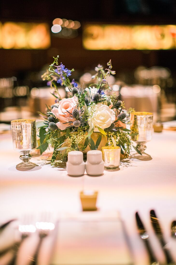 White spray roses and mercury candles were delicately scattered across all the reception tables. The round tables placed around the performance hall were adorned with mercury-glass vases full of seeded eucalyptus, pale pink and white flowers, and blue thistle.