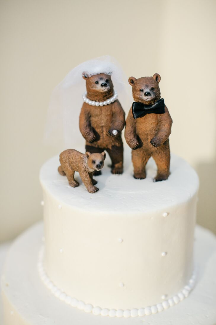 The cake was topped with bears dressed as a bride and groom and a baby bear.