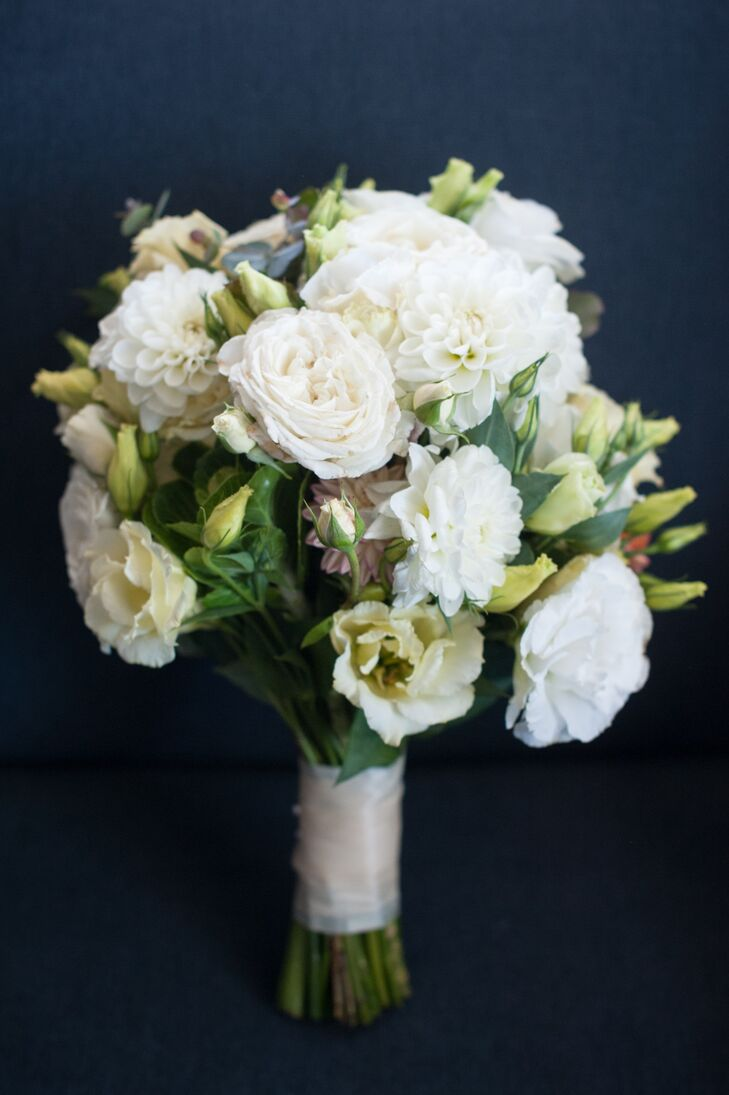 Marguerite carried a loosely-arranged bouquet with white garden roses and white dahlias incorporating light green rosebuds for added color.