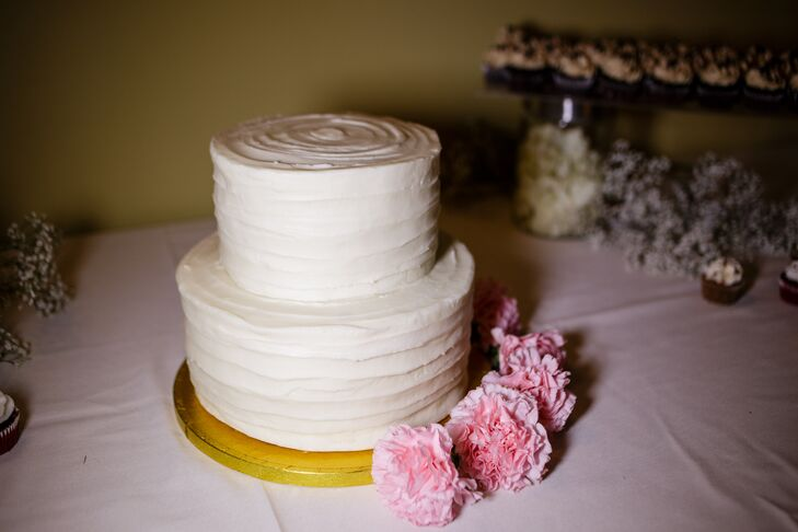 The simple, classic white wedding cake reflected the day's classic theme. The two-tier red velvet cake had buttercream frosting covering its surface, with pink carnations lining the bottom of the gold stand.
