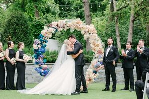 Elegant First Kiss with Circular Wedding Arch and Colorful Flowers