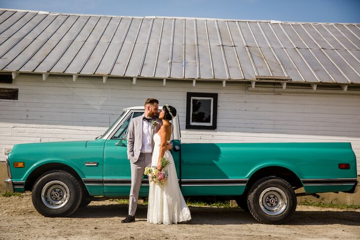 The newlyweds posed for a quick photo alongside of a green pickup truck that was brought in to be displayed by the barn.