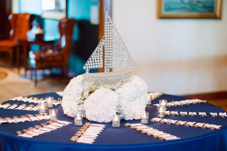 A rhinestone sailboat surrounded by bunches of white hydrangeas was an elegant, nautical centerpiece for the escort card table.