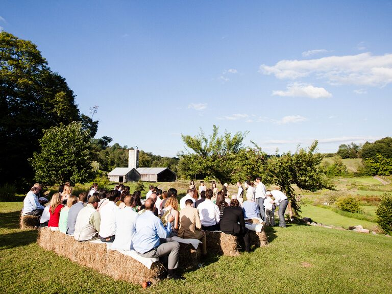 Guests sit on hay bales during the ceremony