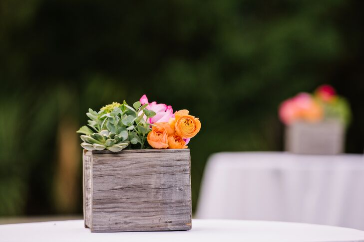 The outdoor cocktail tables had their own natural accents. Each was set with bright orange ranunculus, greenery, succulents and pink peonies inside a wooden breakaway vase.