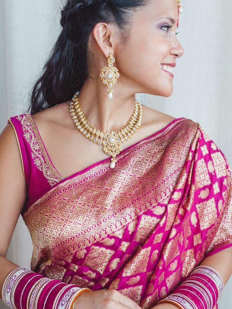 Bride wearing maroon and gold lehenga and saree
