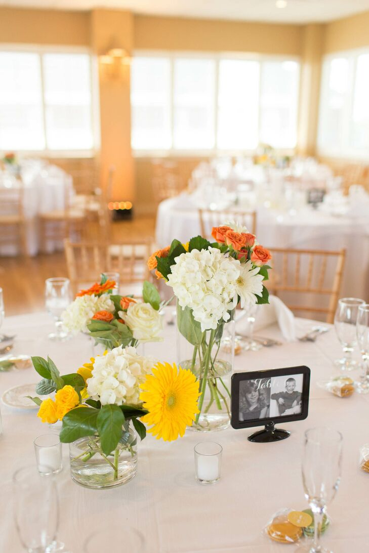 Centerpieces at the Lesner Inn wedding were short glass vases with arrangements of white hydrangeas, yellow gerbera daisies and orange roses. The table numbers were indicated with signs that included pictures of the bride and groom at the same age as the table number.