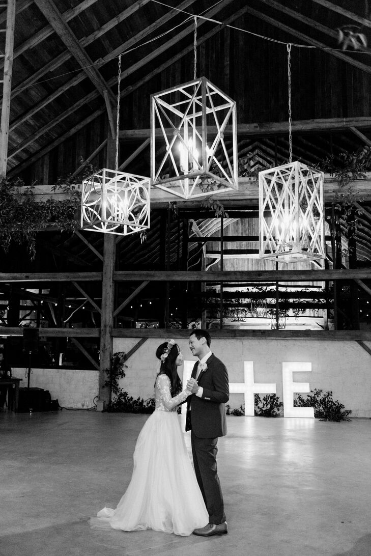 Elton and Deborah had their first dance under geometric chandeliers, which warmed the lofty barn at Chandelier Grove in Tomball, Texas