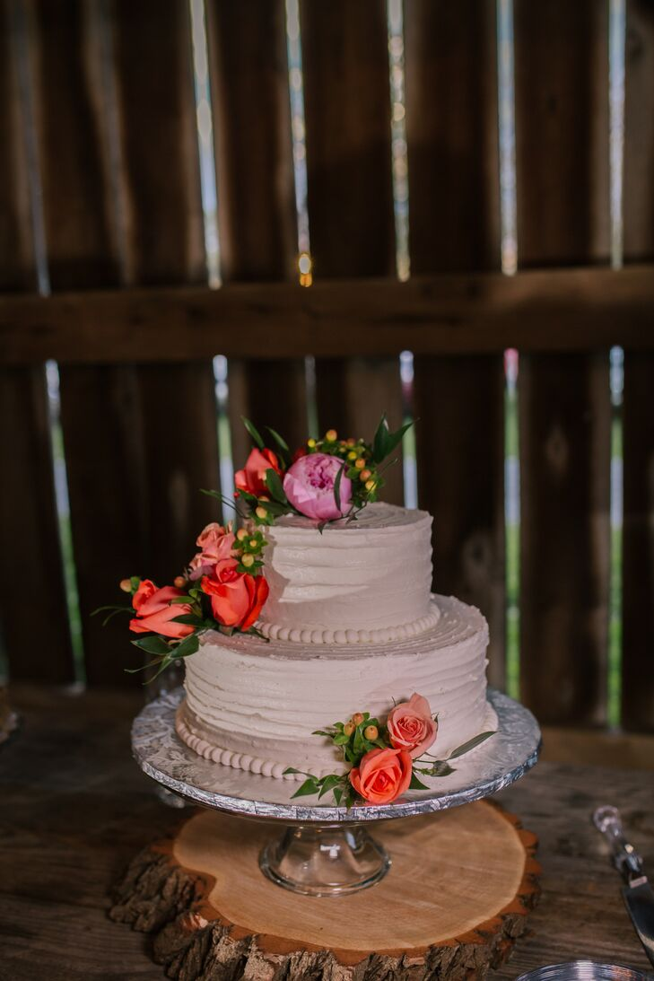 Teresa's Sweet Tooth Confections created a two-tier cake covered in textured white buttercream. Coral and pink flowers added a pop of color to the confection.