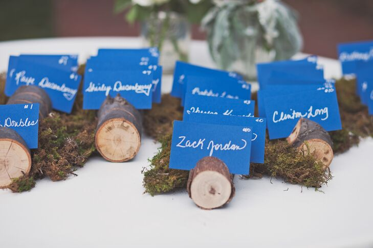 Emily and Alex made all the escort cards themselves using blue stock paper and a silver marker. They were displayed in unfinished wooden rounds surrounded by green moss for a little rustic flair.