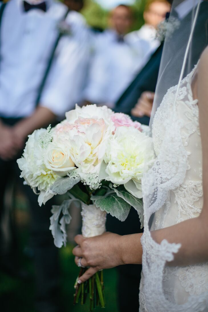 Nicole clutched an arrangement of ivory and blush blooms. The bouquet included roses, peonies and garden roses.