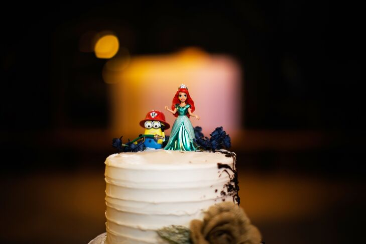 "Instead of the traditional bride and groom cake topper, the couple decorated their cake with a playful accent that was representative of their relationship and story. Aubrey and Robert placed two Disney character figurines on top of their cake, a minion from ""Despicable Me"" and Ariel from ""The Little Mermaid,"" a nod to their Disney World proposal."