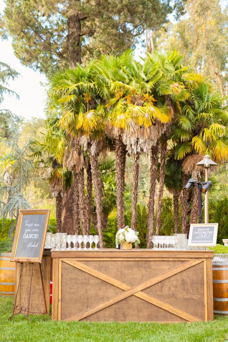After the outdoor ceremony, guests stopped at the textured kraft-wood bar for a glass of champagne. The bar's decor—white blossoms and greenery in a gold mercury-glass vase—were mirrored on the dining tables.