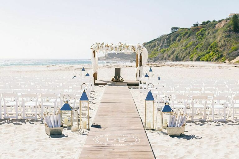 Beach wedding ceremony with white folding chairs, wood walkway and romantic arch