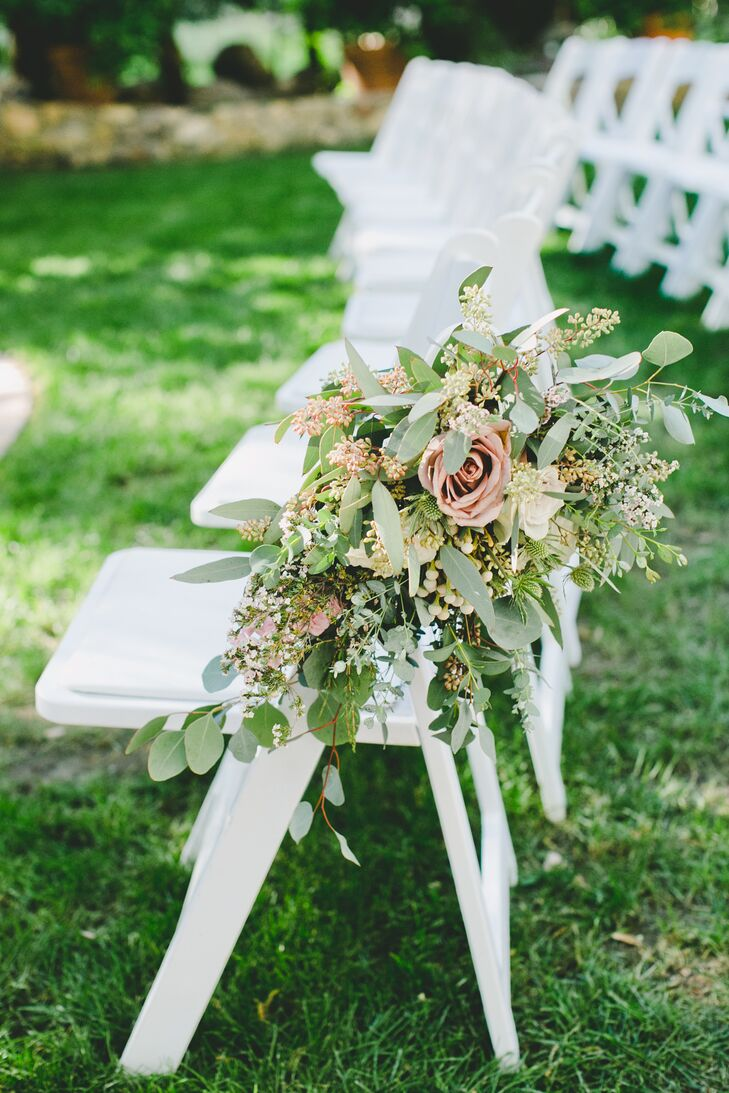 At the ceremony, white folding chairs that lined the aisle had overflowing flower arrangements filled with roses, eucalyptus and leafy greens—contributing to the overall garden-inspired theme of the day.