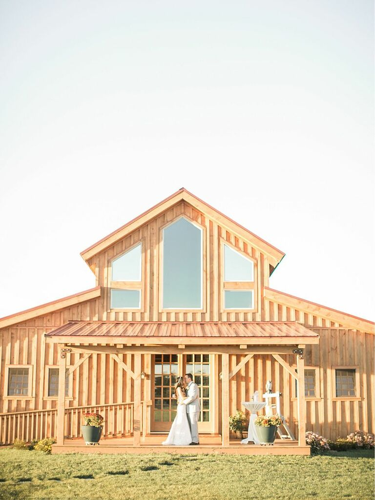 bride and groom in front of rustic modern venue