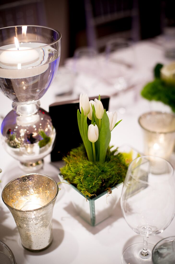 In addition to the larger flower arrangements, there were smaller centerpieces made up of square, mirrored vases. Each one held a white tulips surrounded with mossy greens.