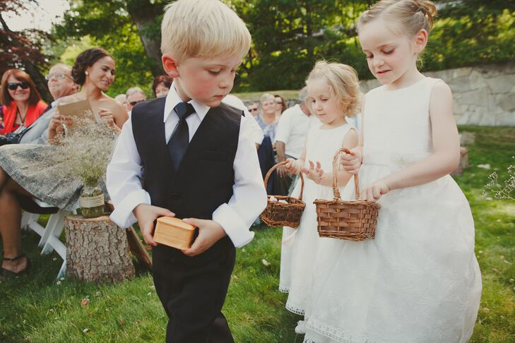 The ring bearer peeked into one of the flower girls' wicker basket as they walked down the aisle together as an adorable little group.