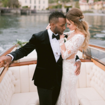 bride in long sleeve lace dress with groom on boat
