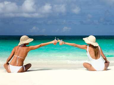 best friends toasting with drinks in the Caribbean