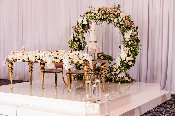 Dramatic Cake Table on Small Stage With Floral Arch Backdrop