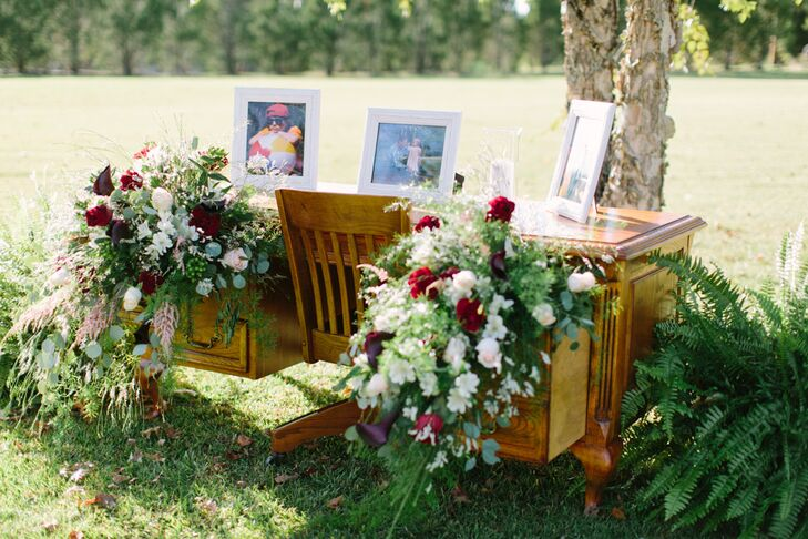 Megan's grandfather's desk served as the memory table. Framed images were placed on the desk, while floral arrangements of red, white and green cascaded out of the drawers.