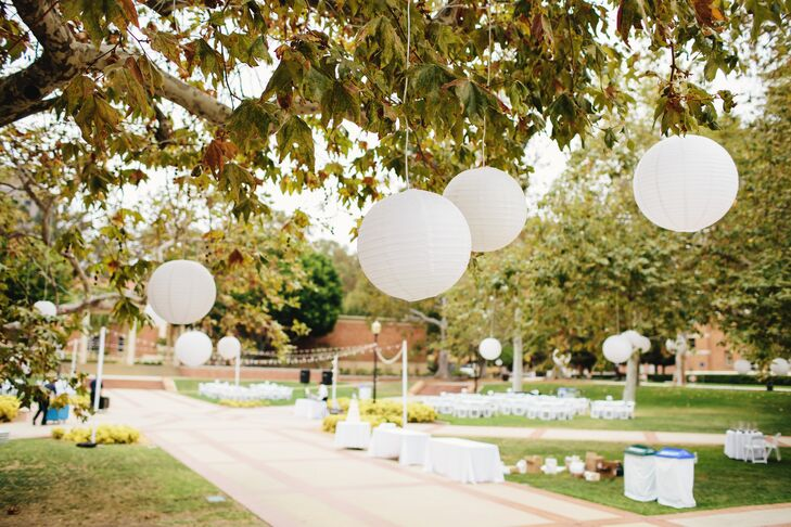 """""""We used mostly white decorations and accents. The flowers were all ivory or white garden roses, wrapped in ivory silk ribbon. The reception area was surrounded by large trees, so we hung large ivory lanterns from the trees for an elegant glow,"""" says the couple."""