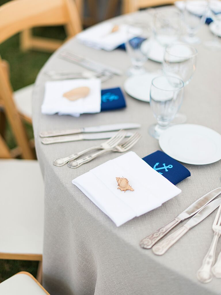 Table setting with blue napkin tablecloth and anchor detail