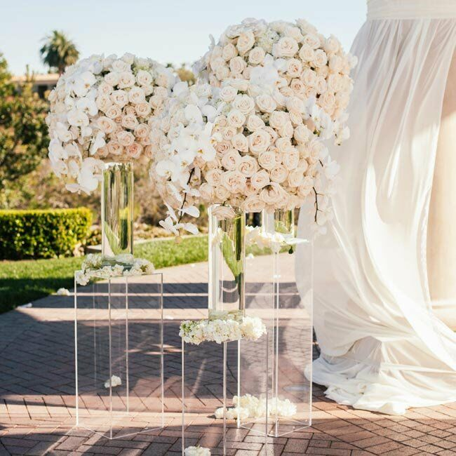 To cut costs on the flowers, we used the reception centerpieces during the ceremony as well, lining the aisle and rotunda with them. It made it seem like there were flowers everywhere and I loved it! says Casey.