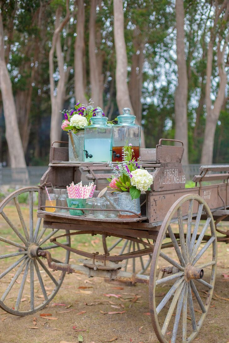 Beverages, mason jars, and colorful straws were offered to guests on a vintage wagon cart.