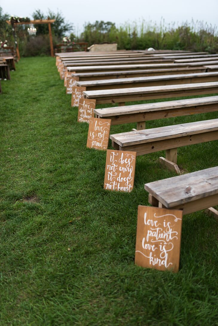 """An eight-foot-tall arbor draped in ivory fabric, a chandelier and a garland with maroon accents was lovingly built by Sarah's dad. Signs lining the aisle displayed verses from 1 Corinthians (""""Love is patient, love is kind"""")."""
