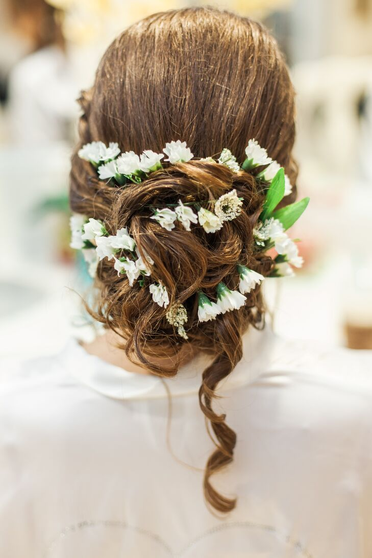 After All Ways Hair Studio styled her curls into a chic updo, they added a few natural accents to match her bouquet. Small white flowers were braided into it as a single curl fell along her back.