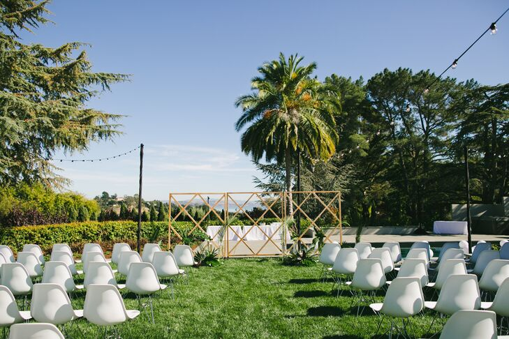 "Modern white Eames-style chairs were set up for the backyard ceremony—they doubled as chairs for the reception dinner—and neutral stone vases held pale yellow king proteas and lots of greenery. ""Scott's parents' house had such a beautiful backdrop that we didn't need to accessorize very much."""