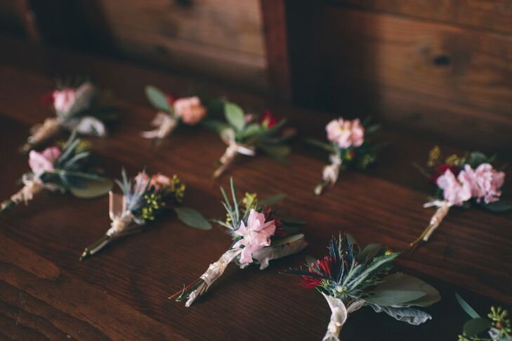 Groomsmen sported boutonnieres made with textured greenery and petite pink and red blooms.