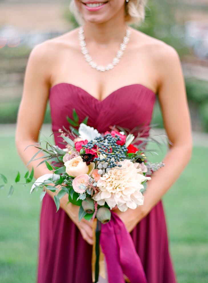 Rose blossoms in cream and soft pink were surrounded with leafy greenery for the bridesmaid bouquets, which subtly complemented their merlot gowns.