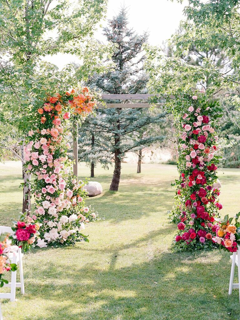 Wedding ceremony arch with orange, fuchsia and pink flowers