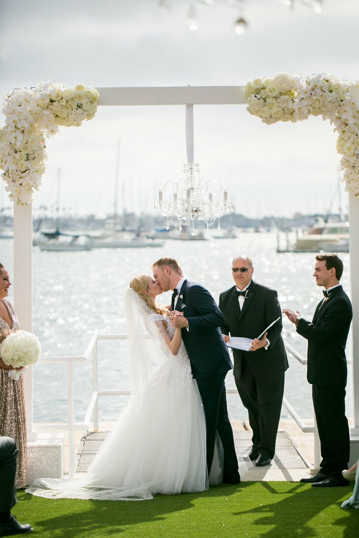 Kelly and Michael have their first kiss as husband and wife under a modern white wedding arch decorated with big bundles of white blossoms.