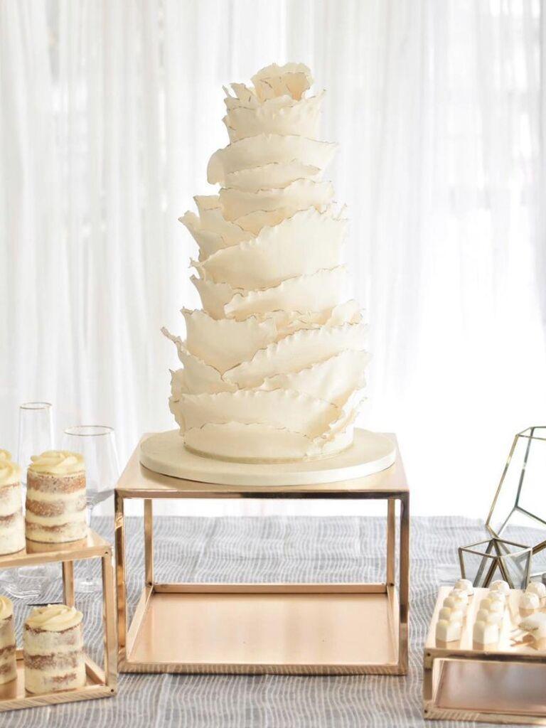 Large square metallic wedding cake base beneath tall cake